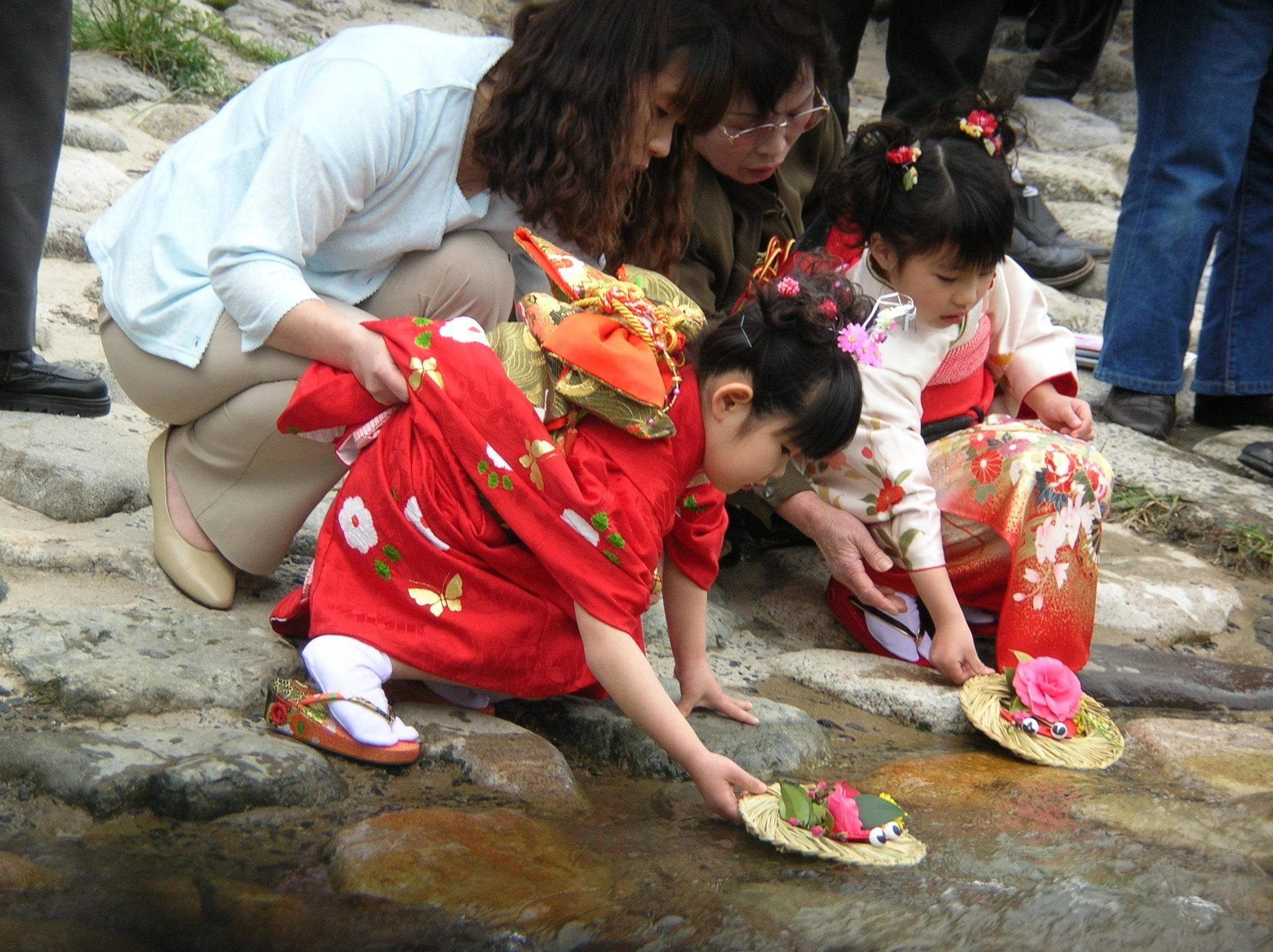 Niñas echando al río las muñecas de papel durante el Hinamatsuri